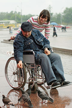 a social worker assisting a wheelchair-bound senior citizen